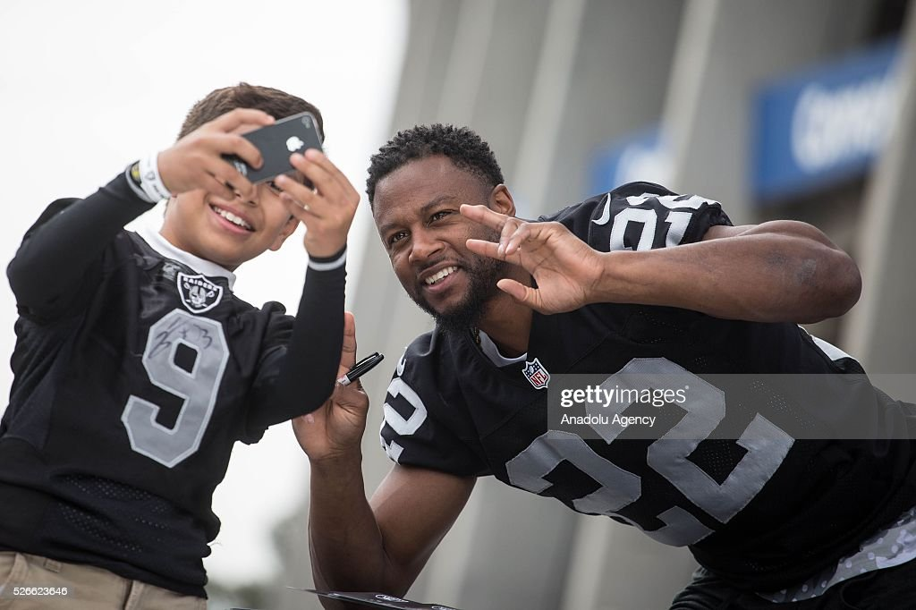 Oakland Raiders Running Back, Taiwan Jones, poses for a picture with a fan during The Oakland Raiders Fan Fest in Mexico City, Mexico on April 30, 2016. Raiders and HoustonTexans will play at the Azteca Stadium next Nov 21, will also be the first Monday Night NFL game played outside the U.S.