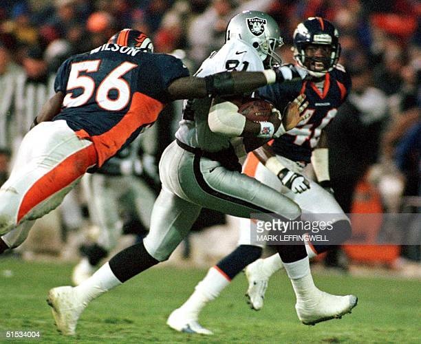 Oakland Raiders' wide receiver Horace Copeland is tackled by Denver Broncos' linebacker Al Wilson and cornerback Dale Carter during the third quarter...