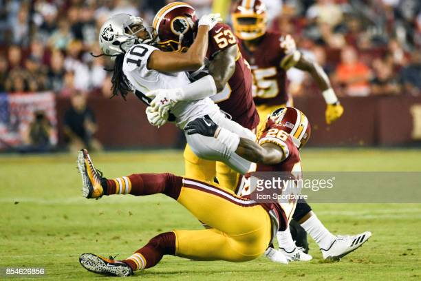 Oakland Raiders wide receiver Seth Roberts catches a pass and is hit by Washington Redskins inside linebacker Zach Brown and cornerback Bashaud...