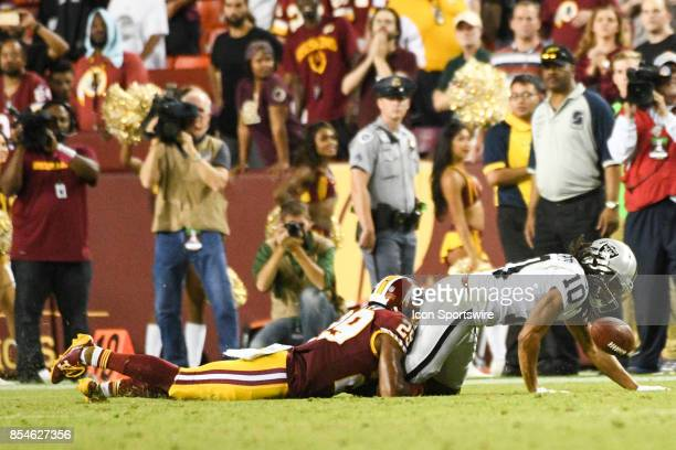 Oakland Raiders wide receiver Seth Roberts fumbles a ball after a pass reception in the fourth quarter on a tackle by Washington Redskins cornerback...