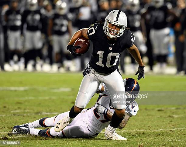 Oakland Raiders wide receiver Seth Roberts picks up a big gain after a catch as Denver Broncos cornerback Bradley Roby hauls him down during the...