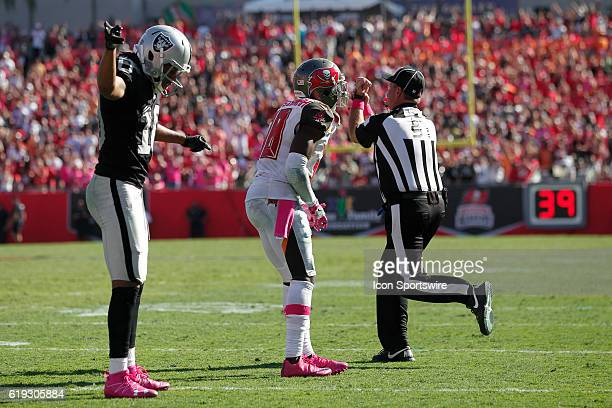 Oakland Raiders wide receiver Seth Roberts signals first down as an unhappy Tampa Bay Buccaneers cornerback Jude AdjeiBarimah reacts to the head...