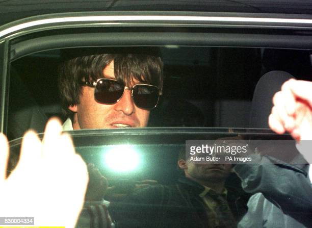 Oasis's Noel Gallagher peeks over a half opened window as he is driven away in a darkened limousine from Gatwick Airport today after the band flew in...