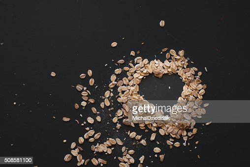 oat flakes heart on dark wooden table : Stock Photo