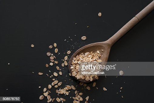 oat flakes on wooden spoon on dark wooden table : Stockfoto