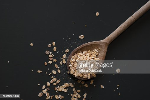oat flakes on wooden spoon on dark wooden table : Bildbanksbilder