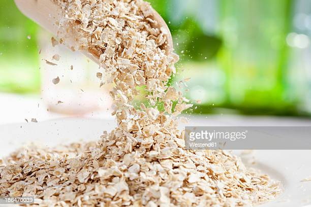 Oat flakes pouring from wooden scoop, close up