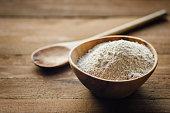 Oat flour in old wooden bowl on dark wooden background