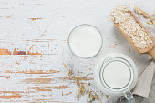 Oat milk in glass and jar on wood background, copy space