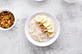 Oats porridge with banana slices and nuts in bowl over stone background. Dish for breakfast. Diet healthy nutrition food concept. Top view, flat lay.