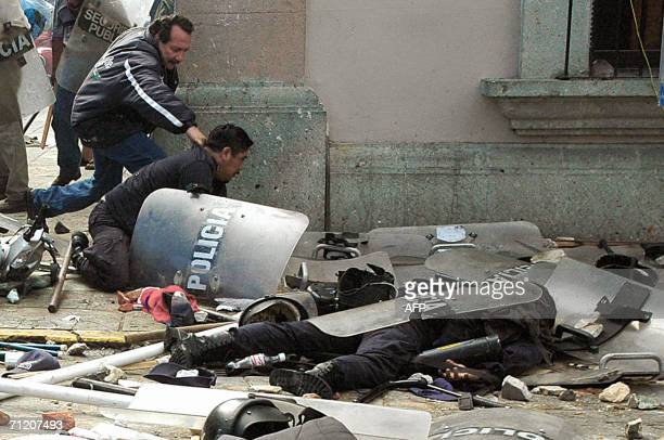 Oaxaca state police officers attempt to rescue a comrade who lies unconscious amid a mess of abandoned shields and helmets during clashes occured...