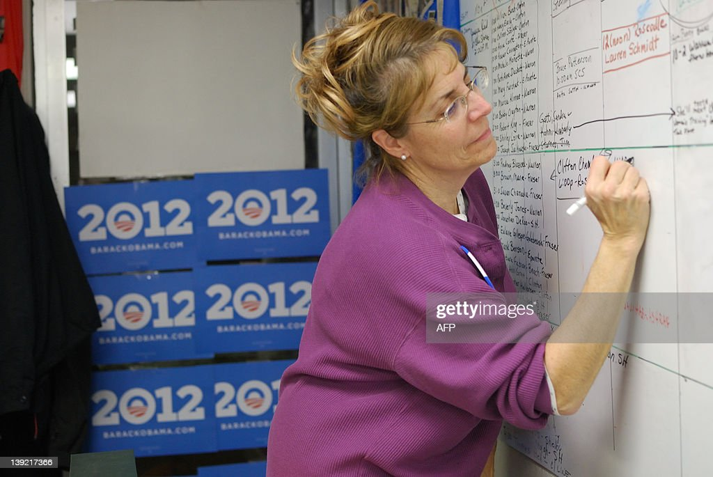 Obama for America volunteer Linda Koch write the name of a new volunteer on the board of the campaign office in Warren, Michigan on February 15, 2012. While the state of the economy will be a major factor in swaying voters, volunteers like Koch could make or break the election by driving turnout in what is expected to be a tight race for the White House. AFP PHOTO / Mira OBERMAN