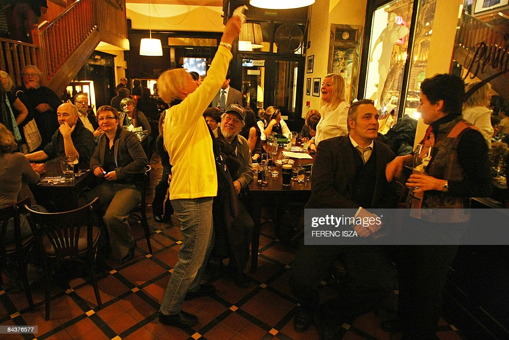 Obama supporters celebrate the inauguration ceremony of Barack Obama in a pub in downtown of Budapest on January 20, 2009. Barack Obama took the oath of office to become the first African-American president in US history on January 20 in Washington DC. From Kogelo to London and Basra, millions were glued to television screens as they watched a new era begin in Washington.