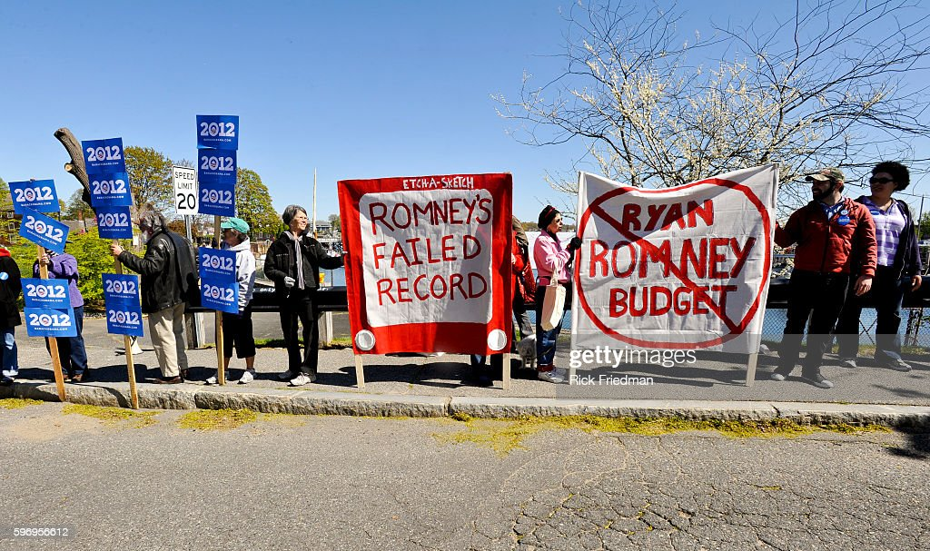 Obama supporters holding signs near a campaign event for Republican Presidential candidate MItt Romney on the fishing docks in Portsmouth NH on April...