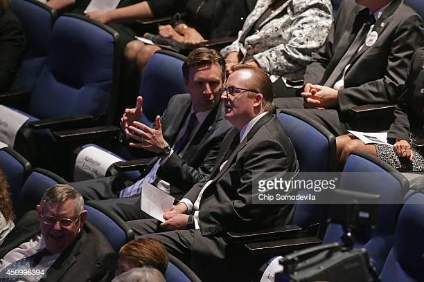 Obama White House Press Secretary Josh Earnest talks with former Press Secretary Robert Gibbs during the memorial ceremony for former White House...