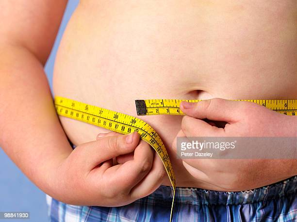 Obese 12 year old boy measuring himself