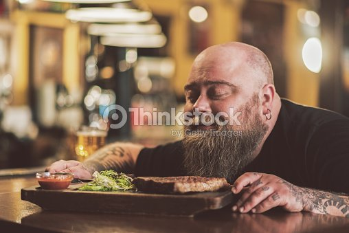 Obese male savoring grilled meat in pub : Stock Photo