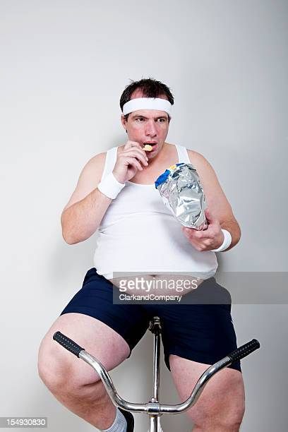 Obese man Eating Potato Chips While Exercising