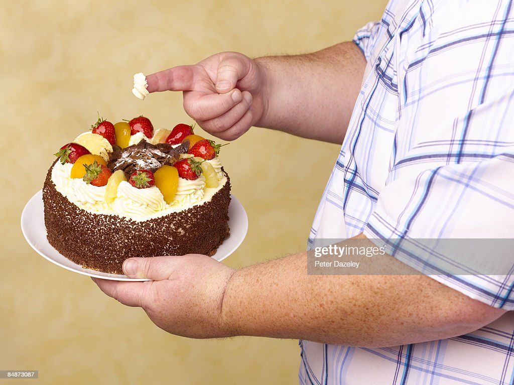 Obese man holding fruit g?teaux with cream on : Stock Photo