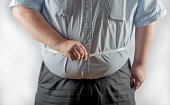 Obese man measuring his waist with a tape measure. UK