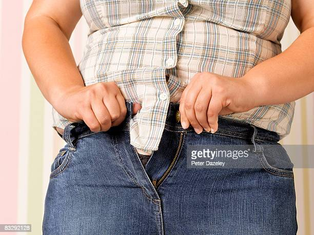 Obese teenager doing up jeans