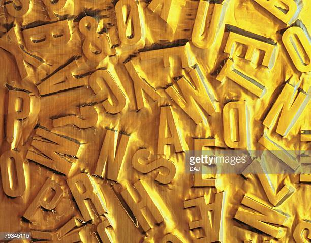 Objects shaped letters covered with gold liquid