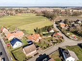 Obliquely photographed aerial view of the edge of a village with houses and a grassy area in the background, which forms a gap in the current location., made with drone