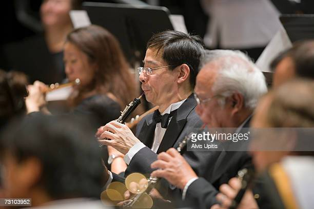 Oboes player in symphony orchestra musicians during performance
