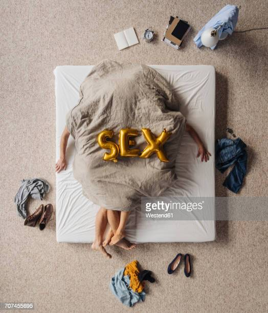 Obscured couple having sex in bed, top view