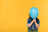 obscured view of child covering face with balloon isolated on yellow