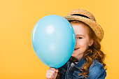 obscured view of smiling child covering face with balloon isolated on yellow