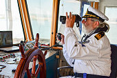 Old experienced captain observes using binoculars by left hand and holding radio comunication equipment by right hand