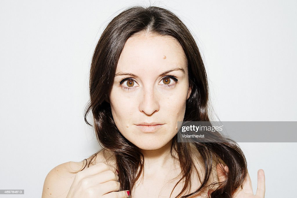 Observing. Beautiful young woman touching her hair : Stock Photo