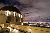 Ultra-wide shot of the large center dome at Griffith Observatory, overlooking downtown Los Angeles at night. Overhead clouds are blurred, downtown skyscrapers are recognizable, as are several major st