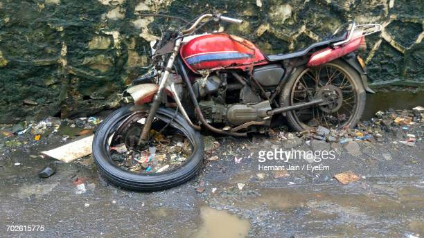Obsolete Motorcycle By Road Against Wall During Rainy Season