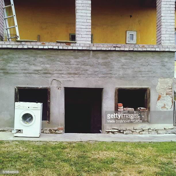 Obsolete Washing Machine In Front Of Abandoned House