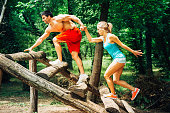 Young muscular couple climbing wooden obstacle on a fitness trail
