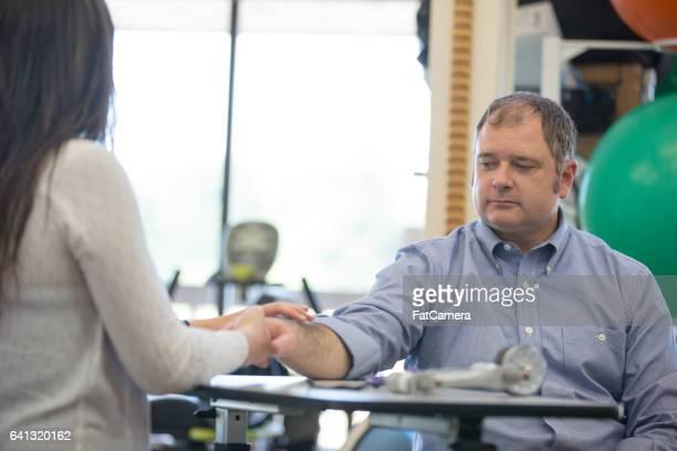 Occcupational-Therapeutin hilft Mann mit Hand Übungen