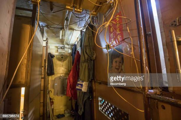 Occupants' possessions hang outside subdivided residential units known as 'coffin homes' that line a a corridor inside a building in Hong Kong China...