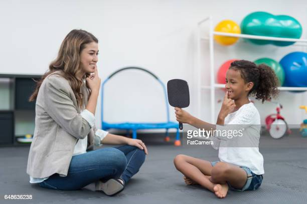 Occupational therapist doing exercise with young African American girl