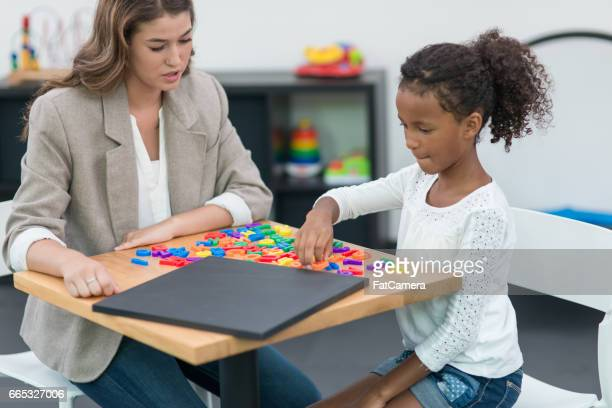 Occupational therapist working with children in modern, playful clinic setting