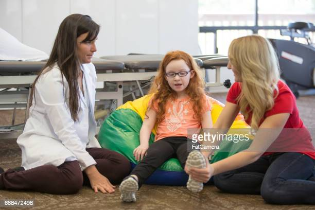 Occupational therapist works with young girl and mother on leg strengthening exercise