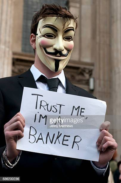 Occupy London Stock Exchange Protester wearing Guy Fawkes mask holding sign saying 'Trust me I'm a banker'