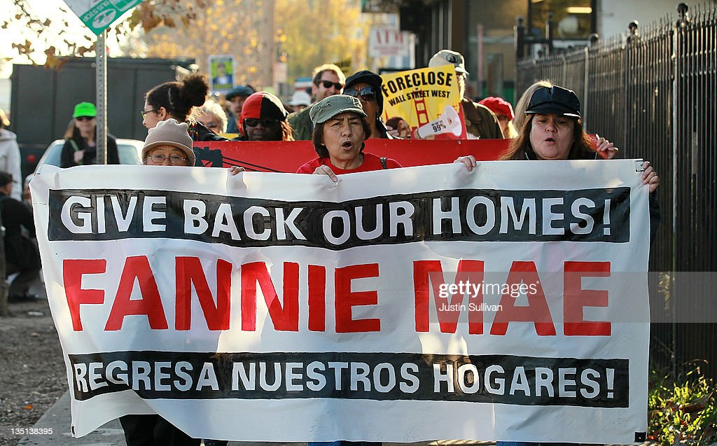 Occupy protesters carry a banner as they march to a foreclosed home that they are going to re-occupy on December 6, 2011 in Oakland, California. Occupy Wall Street groups across the country are staging a day of action against home foreclosures and are protesting outside banks and attempting to re-occupy homes that have been foreclosed.