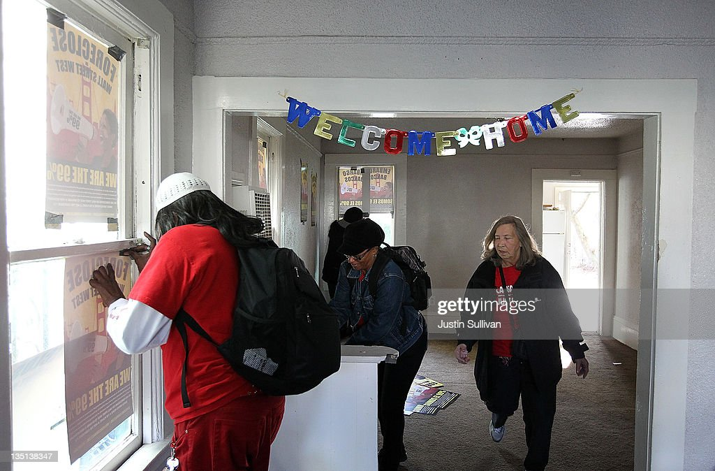 Occupy protesters hang posters on windows in a foreclosed home that they re-occupied on December 6, 2011 in Oakland, California. Occupy Wall Street groups across the country are staging a day of action against home foreclosures and are protesting outside banks and attempting to re-occupy homes that have been foreclosed.
