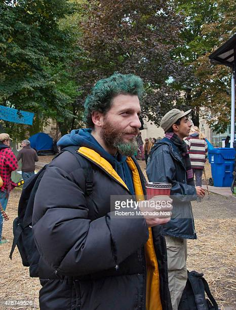Occupy Toronto scenesMan with green hair and beard holds a coffee cup while exploring the park along with other tourists