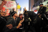Occupy Wall Street participants give peace signs as mounted police is called to stop them trying to break trough police barricade set block them to...