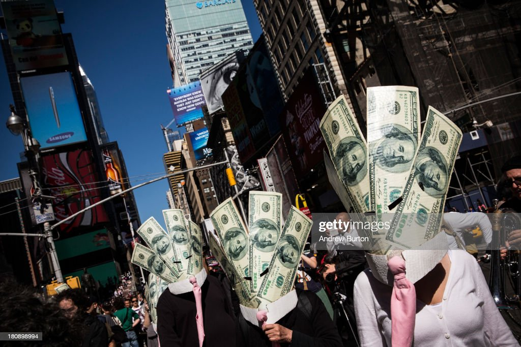 Occupy Wall Street protesters wearing masks made out of enlarged dollar bills act in a short skit in Times Square on September 17, 2013 in New York City. Today marks the two year anniversary since the protestors set up camp in New York's financial district, calling for drastic social and finanical reform.
