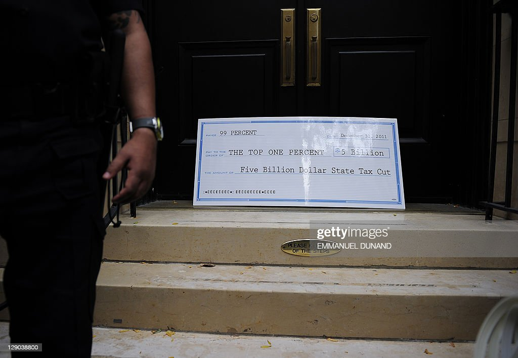 Occupy Wall Street protestors drop an oversize bank check in front of the house of hedge fund manager John Paulson as they stage a 'Millionaires...