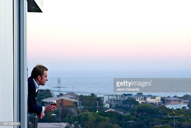 A businessman drinks a glass of wine at sunset from his balcony.